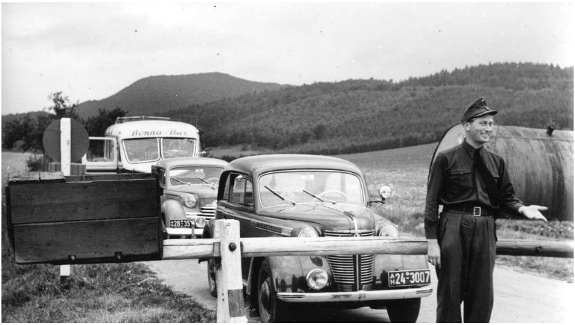 In 1952, an officer of the Federal Border Guard stands in front of the closed barrier on the German-German border near Heldra.